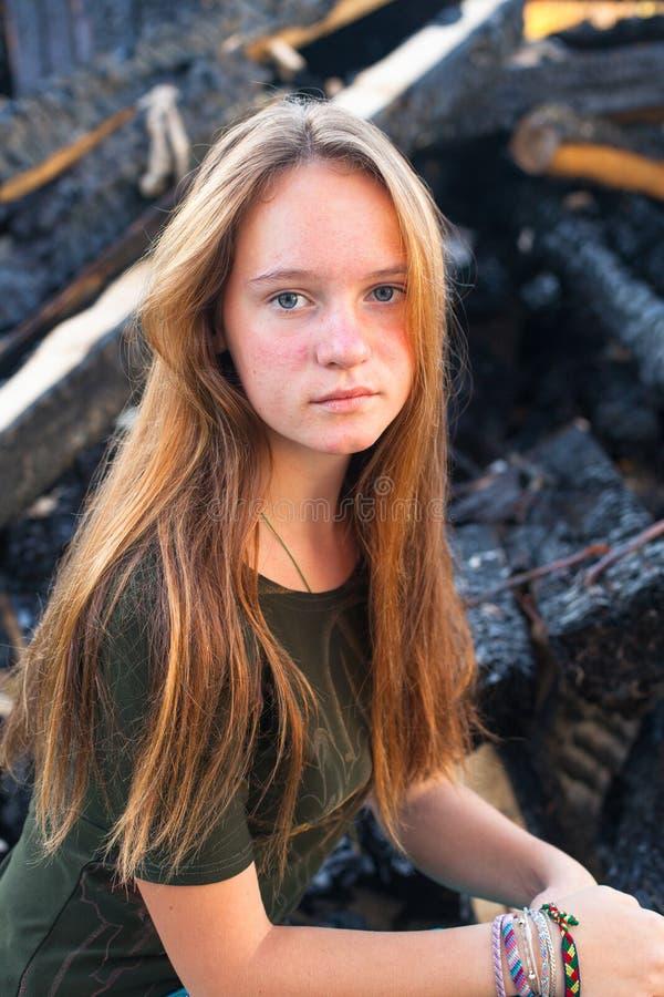 Mädchen nahe den Kohlen von der Feuersbrunst im Hintergrund lizenzfreie stockfotos
