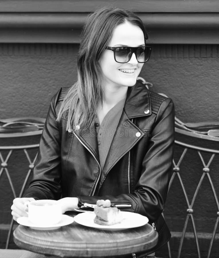 Mädchen nahe geschmackvollem Beerenkuchen und -kaffee auf Tabelle auf braunem Terrassenhintergrund Dame trinkt Kaffee während der lizenzfreies stockfoto