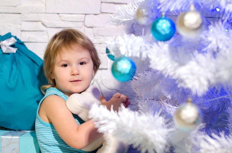 Mädchen nahe Weihnachtsbaum lizenzfreie stockfotos