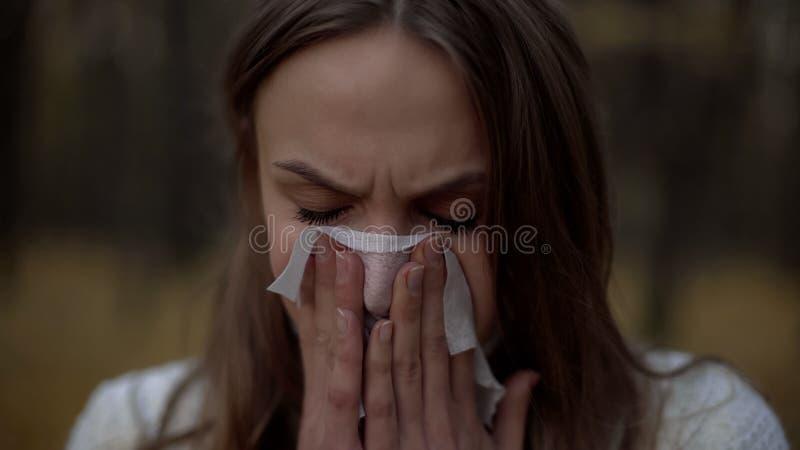 Mädchen niest in Serviette, Beginn der Grippeepidemie im kalten Herbst, Nahaufnahme lizenzfreie stockfotografie