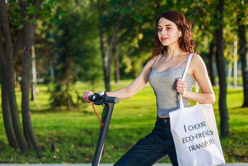 Mädchen nimmt ihren E-Scooter mit Tasche auf der Schulter mit Text: Ich wähle umweltfreundlichen Verkehr lizenzfreie stockfotografie