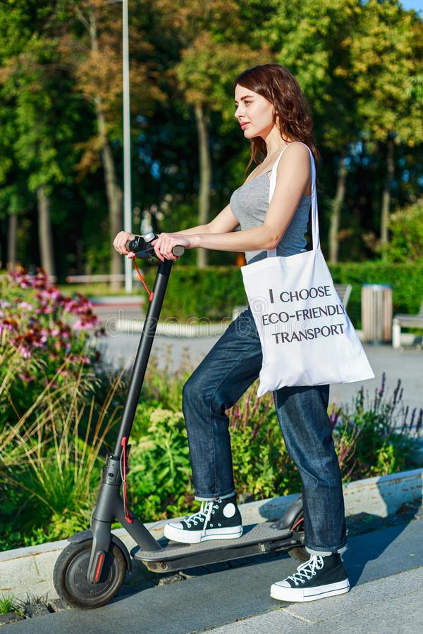 Mädchen nimmt ihren E-Scooter mit Tasche auf der Schulter mit Text: Ich wähle umweltfreundlichen Verkehr stockfotos