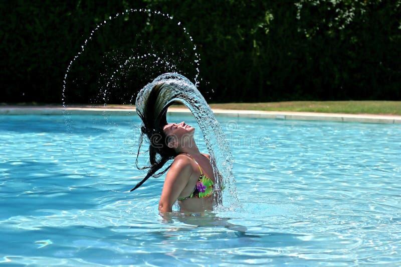 Mädchen oder Frau im Swimmingpool, der zurück nasses Haar wirft stockfoto