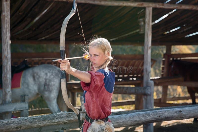 Mädchen oder nettes Frauen-, Bogenschütze- oder Jägerschießen mit Pfeil und Bogen am sonnigen Tag am stabilen Ziel auf Heuballen  stockfotos