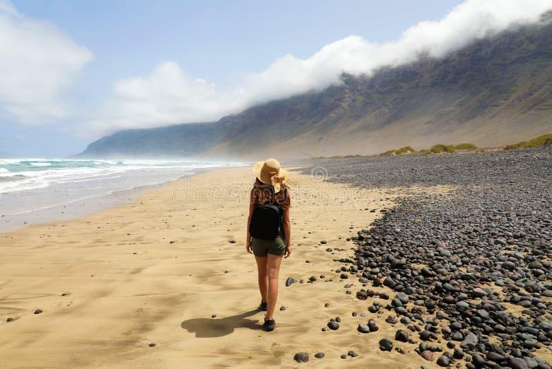 Mädchen passt die andeutende Landschaft von Caleta Famara, Lanzarote, Kanarische Inseln auf stockfoto