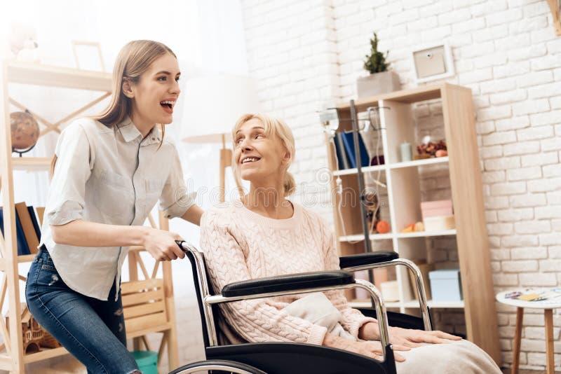 Mädchen pflegt ältere Frau zu Hause Mädchen reitet Frau im Rollstuhl stockfotografie
