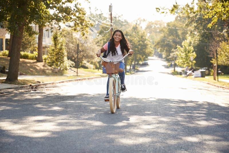 Mädchen-Reitfahrrad entlang Straße zur Schule lizenzfreie stockbilder