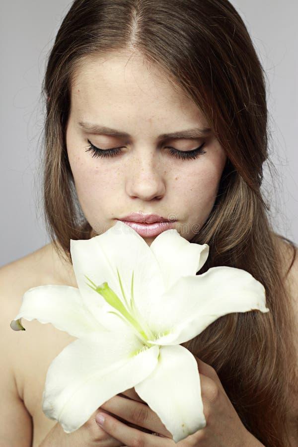 Mädchen riecht eine Lilie stockbild