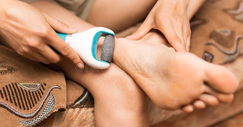 Mädchen säubert die Ferse auf dem Fuß lizenzfreies stockbild