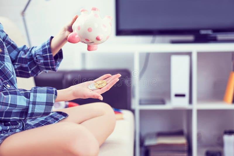 Mädchen ` s übergibt das Halten von einem Sparschwein und das Gießen von bitcoins aus ihm heraus Konzept des Falles in den Wert v stockfoto