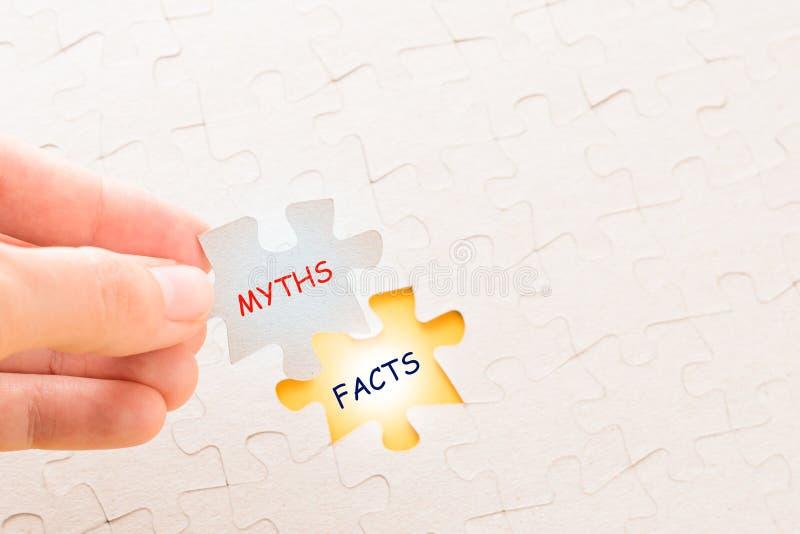 Mädchen ` s Hand, die das letzte Puzzlestück mit Wort Tatsachen und Mythen setzt lizenzfreie stockfotos