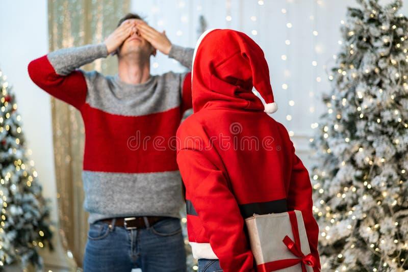 Mädchen in Sankt-Strickjacke werden fertig, ein Geschenk zu geben und der Kerl wartet, seine Augen mit seinen Händen bedeckend stockbild