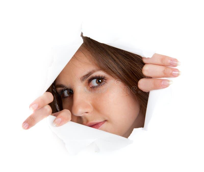 Mädchen schaut durch ein Loch stockbild