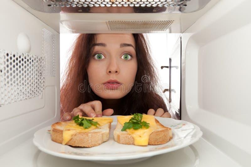 Mädchen schaut in einer Mikrowelle stockfotografie