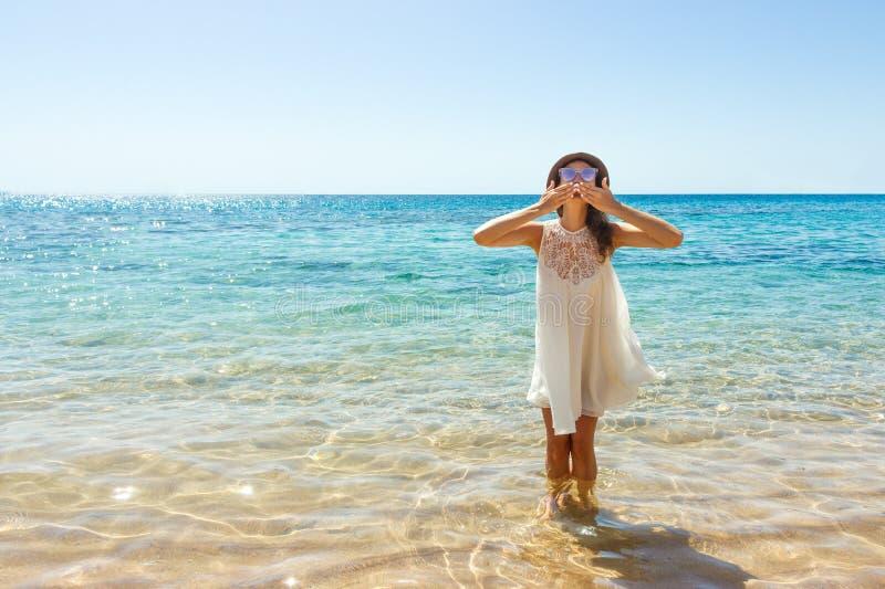 Mädchen schickt einen Luftkuß zur Kamera eine schöne sorglose Frau, die am Strand genießt ihr weißes Kleid der Sonne sich entspan lizenzfreies stockbild