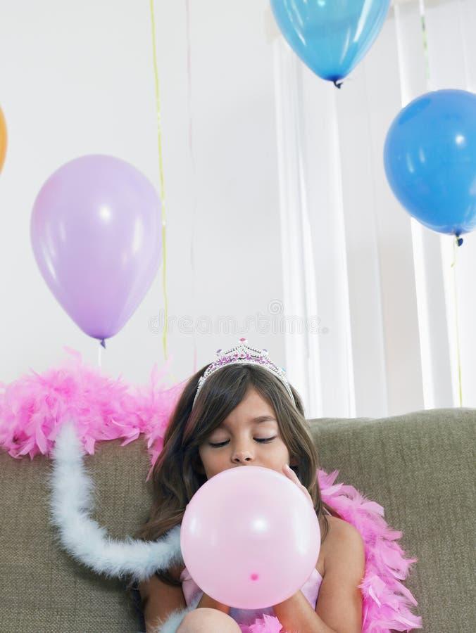 Mädchen-Schlagballon auf Sofa stockfoto