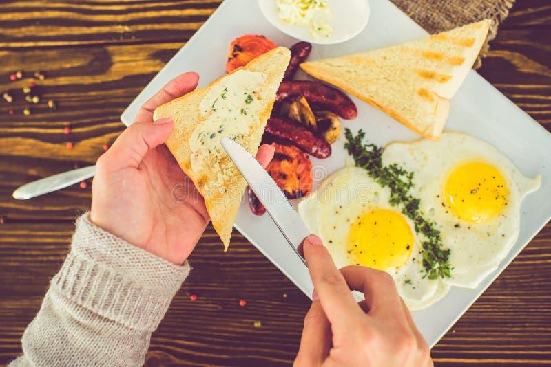 Mädchen schmiert Butter mit einem Messer auf einem dreieckigen gebratenen Toast Frühstück von Spiegeleiern mit Toast stockfotografie