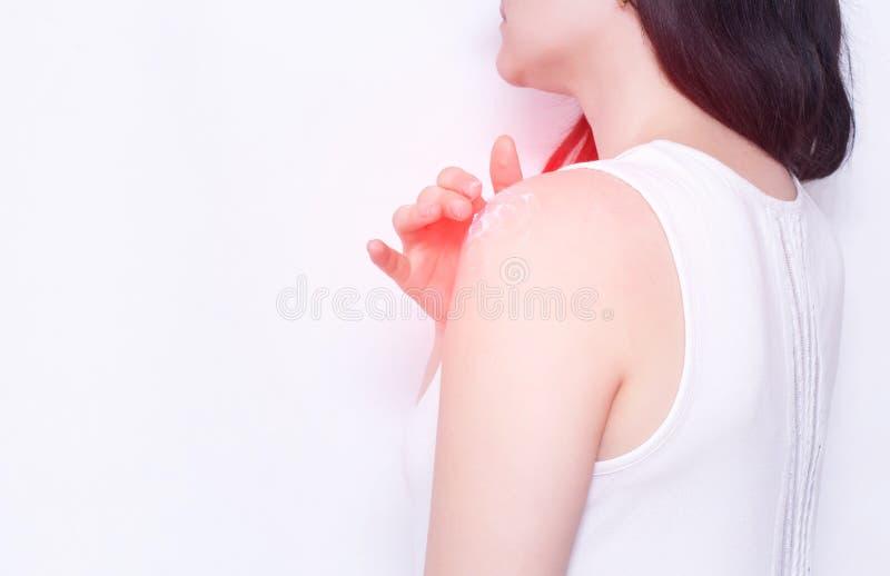 Mädchen schmiert ein wundes Schultergelenk mit entzündungshemmender Salbe, um die Schmerz und Entzündung, Kopienraum, Rheumatismu lizenzfreie stockfotos