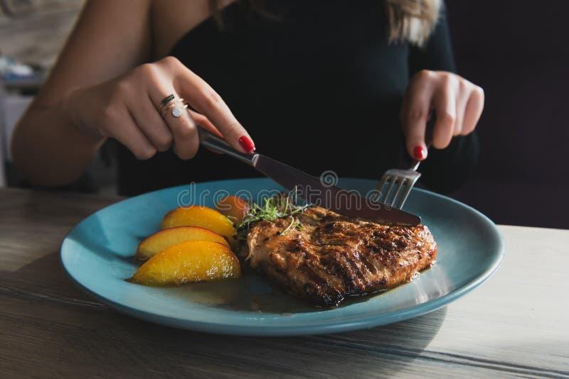 Mädchen schneidet saftiges gegrilltes Truthahnsteak mit Messer und Gabel stockfoto