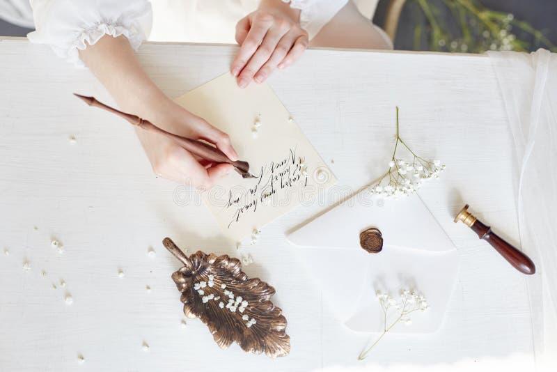 Mädchen schreibt ihrem geliebten Mann einen Brief und zu Hause sitzt bei Tisch in in einem Kleid, einer Reinheit und einer Unschu lizenzfreie stockbilder