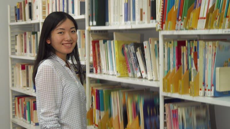 Mädchen setzt akademische Zeitschriften auf das Gestell an der Bibliothek stockbild