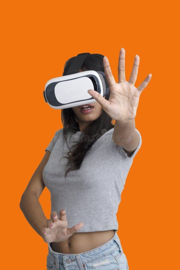 Mädchen setzte ihre Hände, um etwas beim Spielen des Multimediaspiels mit Gläsern der virtuellen Realität zu fangen lizenzfreie stockfotografie