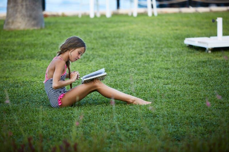 Mädchen sind Lesebuch an der Sommergrünwiese lizenzfreie stockbilder