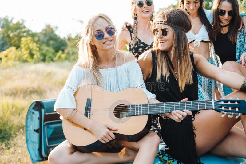 Mädchen sitzen auf dem Stamm mit einer Gitarre lizenzfreies stockfoto