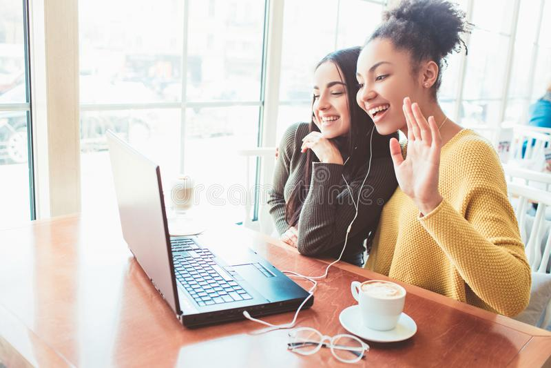 Mädchen sitzen im Café und plaudern mit jemand Vermutlich es ` s ihr dritter Freund, der ` t mit ihnen sein kann jung stockfoto