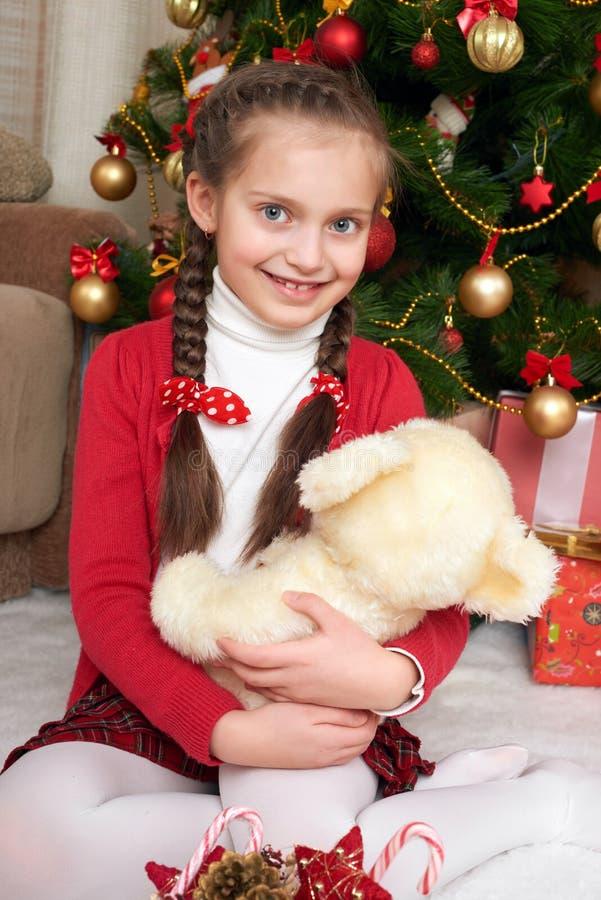 Mädchen sitzen nahe Weihnachtstannenbaum und mit Bären, Weihnachtsdekoration zu Hause spielen, glückliches Gefühl, Winterurlaubko lizenzfreie stockfotos
