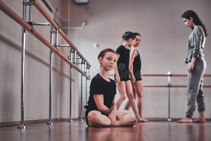 Mädchen sitzt auf dem Boden während ihre anderen Mitschüler, die Übungen mit Trainer tun stockfotografie