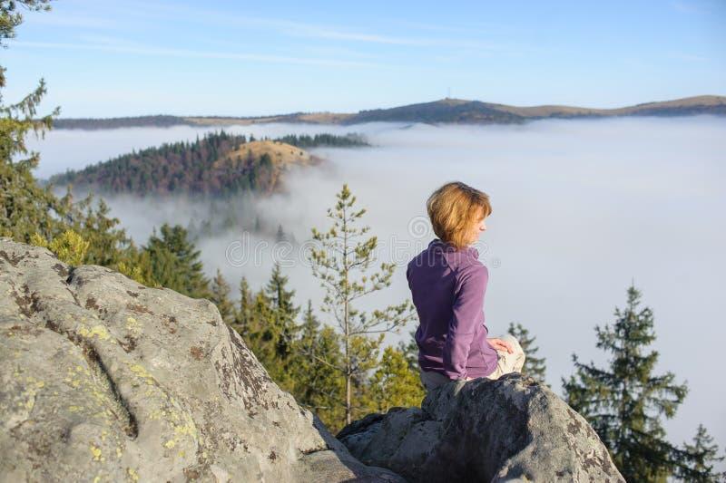 Mädchen sitzt auf einen Berg und schaut um ungefähr lizenzfreie stockfotos