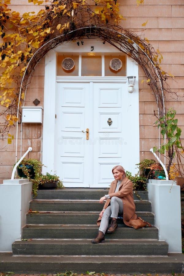 Mädchen sitzt an den Türen eines alten Hauses Spätherbstabend lizenzfreie stockbilder