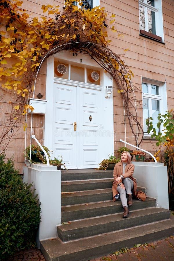 Mädchen sitzt an den Türen eines alten Hauses Spätherbstabend stockbilder