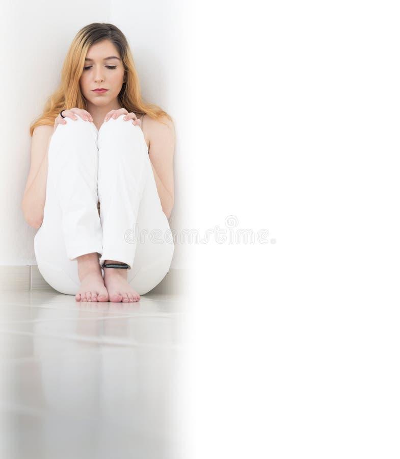 Mädchen sitzt in der Ecke und geduckt Der Raum ist leeres stockfotos