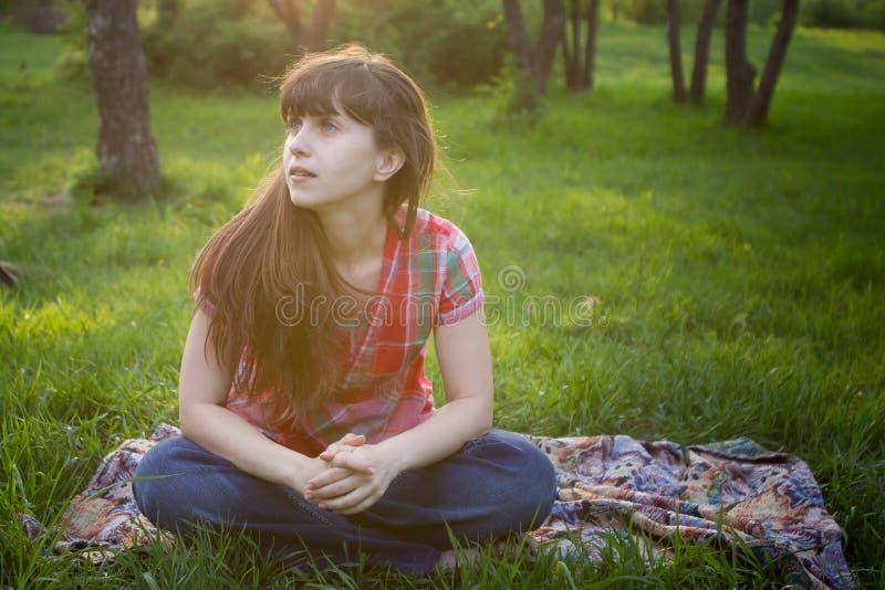 Mädchen sitzt in einem Park stockfotos