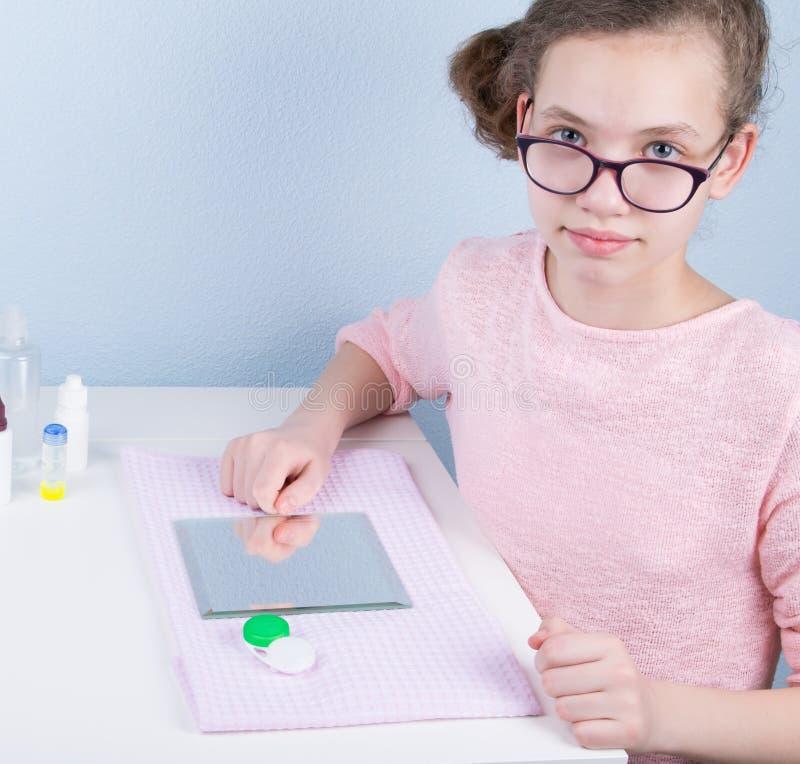 Mädchen sitzt an einem Tisch mit Gläsern, vor einem Spiegel, um sie zu den Kontaktlinsen zu ändern lizenzfreie stockbilder
