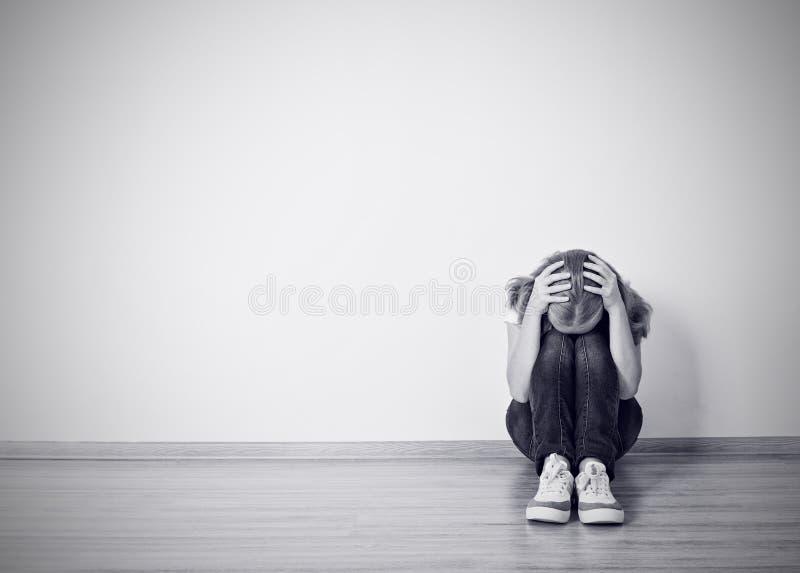 Mädchen sitzt in einer Krise auf dem Boden nahe der Wand stockbild