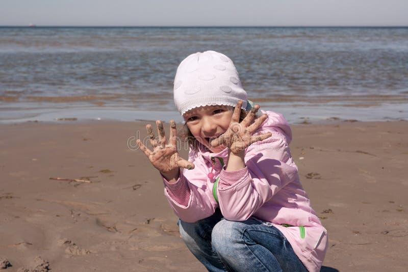 Mädchen spielt auf dem Seeufer lizenzfreie stockbilder