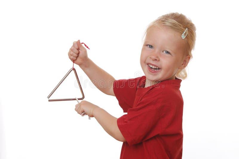 Mädchen spielt Dreieck stockfotos