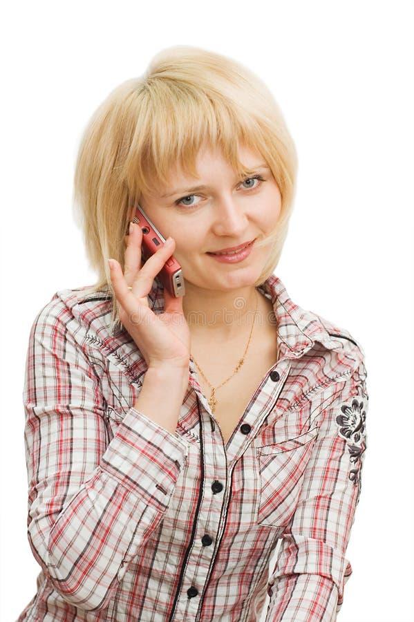 Mädchen spricht durch das Telefon, das über Weiß getrennt wird lizenzfreies stockfoto