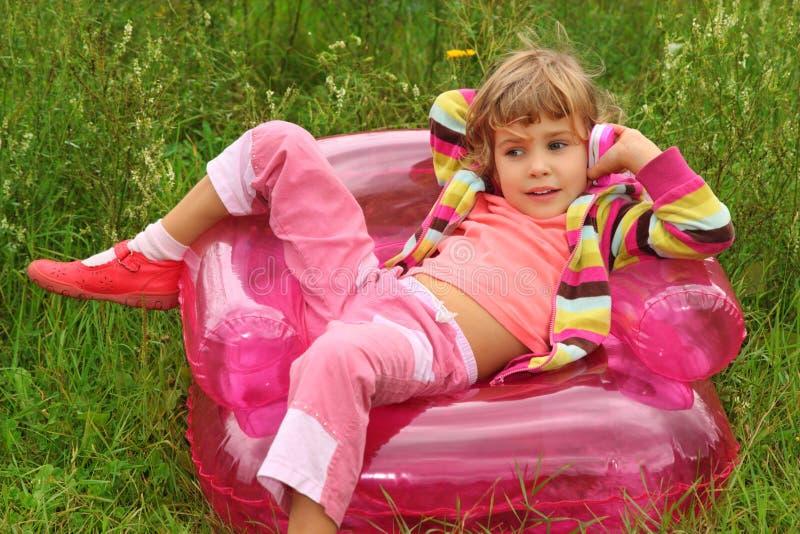 Mädchen spricht durch Spielzeugtelefon im aufblasbaren Lehnsessel stockfoto