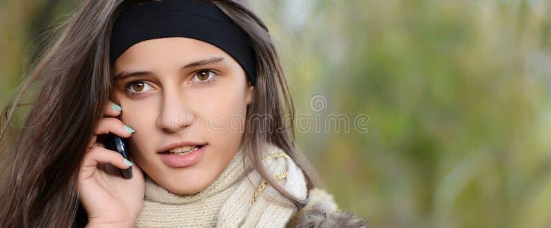 Mädchen spricht durch Telefon im Herbst lizenzfreie stockbilder
