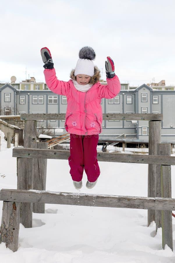 Mädchen springt von der Holzbank lizenzfreie stockfotografie
