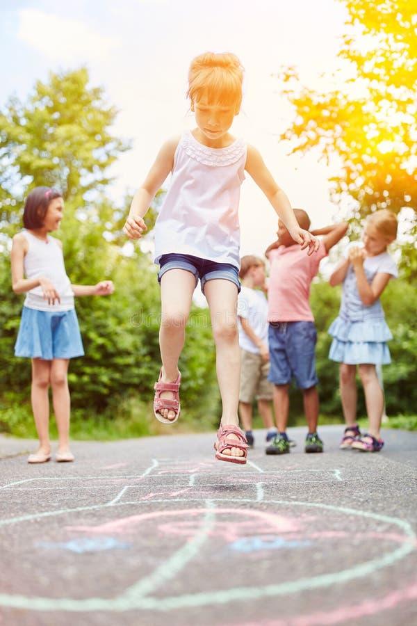 Mädchen springt während des Hopsespiels lizenzfreie stockfotos