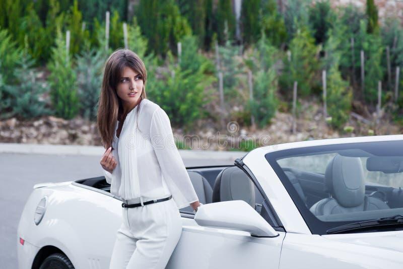 Mädchen steht nahe dem weißen Kabriolett stockbilder