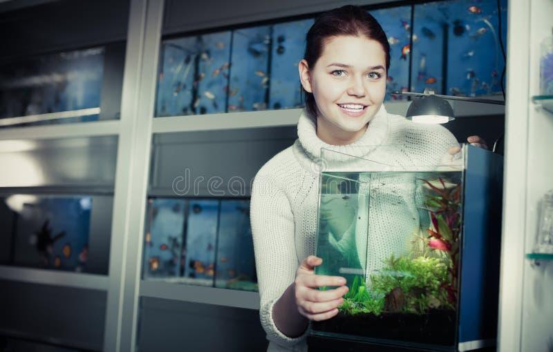Mädchen steht nahe einem Aquarium lizenzfreies stockfoto