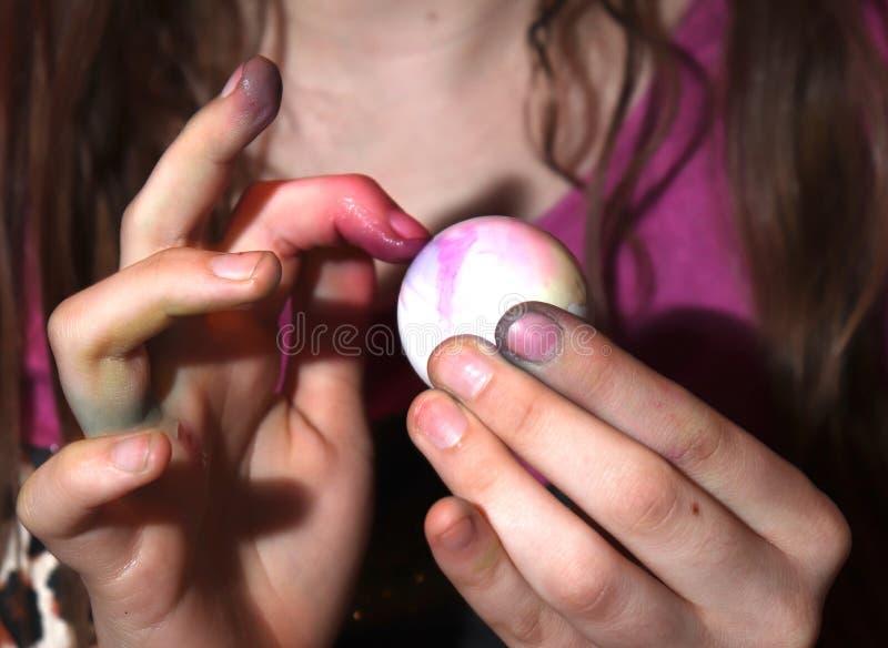 Mädchen-sterbende Ostereier und ihre Finger lizenzfreie stockfotografie