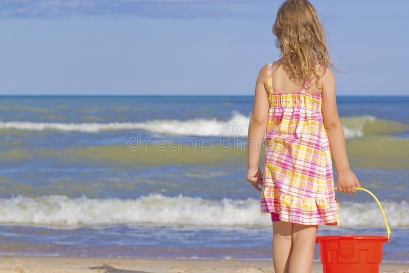Mädchen am Strand mit Wanne. lizenzfreie stockfotografie