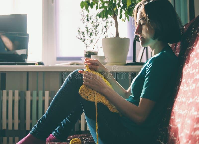 Mädchen strickt Häkelarbeit zu Hause lizenzfreie stockfotos